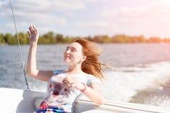 Giovane donna rilassata con gli occhi chiusi di piacere che si siedono sulla barca a vela, godenti della crociera delicata di luc Immagini Stock Libere da Diritti