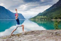 giovane donna rilassata di yoga nella posa di yoga vicino al lago Fotografie Stock Libere da Diritti