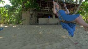 Giovane donna rilassata nelle oscillazioni blu del vestito sull'oscillazione della corda sulla spiaggia sabbiosa calma il giorno  video d archivio