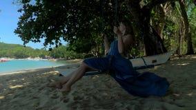 Giovane donna rilassata nelle oscillazioni blu del vestito sull'oscillazione della corda sulla spiaggia sabbiosa calma il giorno  archivi video