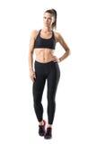 Giovane donna risoluta attraente di misura in abbigliamento di sport che posa con la mano sull'anca immagini stock