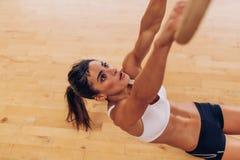 Giovane donna risoluta che si esercita con gli anelli relativi alla ginnastica Fotografia Stock