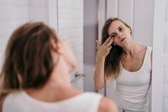 Giovane donna rispecchiata per vedere il suo fronte cominciare ad invecchiare immagine stock