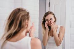 Giovane donna rispecchiata per vedere il suo fronte cominciare ad invecchiare fotografia stock