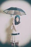 Giovane donna in ritratto di stile 70s con l'ombrello in studio Fotografia Stock