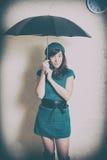 Giovane donna in ritratto di stile 70s con l'ombrello in studio Immagini Stock Libere da Diritti