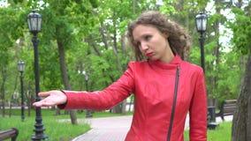 Giovane donna in rivestimento rosso che invita qualcuno a venire in parco video d archivio