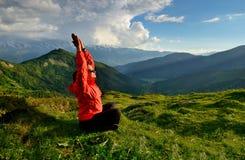 Giovane donna in rivestimento rosso che si siede nella posa di yoga in montagne Immagine Stock