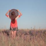 Giovane donna romantica in cappello che sta sul prato nel giorno di estate caldo Fotografia Stock