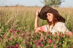 Giovane donna romantica in cappello che sta sul prato nel giorno di estate caldo Fotografie Stock