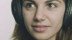 Giovane donna romantica che ascolta la musica sulle cuffie stock footage