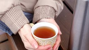 Giovane donna romantica che si rilassa sulla spiaggia con, sul tè o sul caffè caldo bevente dal termos Sera calma e accogliente Fotografia Stock