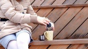Giovane donna romantica che si rilassa sulla spiaggia con, sul tè o sul caffè caldo bevente dal termos Sera calma e accogliente Immagine Stock Libera da Diritti