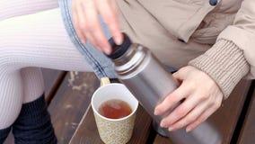 Giovane donna romantica che si rilassa sulla spiaggia con, sul tè o sul caffè caldo bevente dal termos Sera calma e accogliente Immagini Stock
