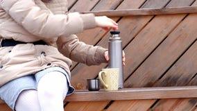 Giovane donna romantica che si rilassa sulla spiaggia con, sul tè o sul caffè caldo bevente dal termos Sera calma e accogliente Fotografie Stock Libere da Diritti
