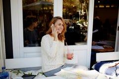 Giovane donna rossa felice dei capelli che per mezzo del telefono delle cellule per la chiamata al suo amico mentre sedendosi in  Fotografia Stock
