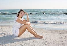 Giovane donna, sedersi rilassata sulla spiaggia fotografia stock libera da diritti