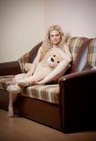 Giovane donna sensuale bionda che si siede sul sofà che si rilassa con un orsacchiotto enorme Immagini Stock