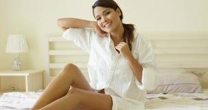 Giovane donna sensuale che allunga sul suo letto video d archivio
