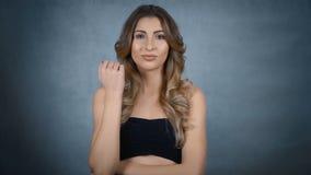 Giovane donna sensuale con il fronte perfetto isolato su fondo grigio stock footage