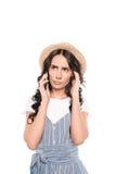Giovane donna seria in cappello di paglia che parla sullo smartphone Immagini Stock Libere da Diritti