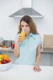 Giovane donna seria che beve un vetro di succo d'arancia Fotografie Stock