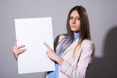 Giovane donna seria che indica allo strato bianco Immagine Stock Libera da Diritti