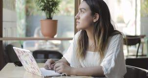 Giovane donna seria che lavora ad un computer portatile video d archivio