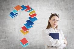 Giovane donna seria con un libro, punto interrogativo Fotografia Stock Libera da Diritti