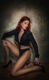 Giovane donna sexy attraente in camicia nera e mutandine che si siedono su un mucchio dei libri sul pavimento Testarossa sensuale immagini stock