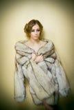 Giovane donna sexy attraente che porta una pelliccia che posa provocatorio dell'interno Ritratto della femmina sensuale con tagli Immagini Stock Libere da Diritti