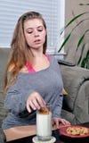 Giovane donna sexy che mangia latte ed i biscotti Immagini Stock Libere da Diritti