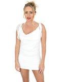 Giovane donna sexy che porta breve vestito bianco che esamina macchina fotografica Fotografie Stock Libere da Diritti