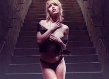 Giovane donna sexy che posa provocatorio alle scale fotografia stock