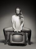 Giovane donna sexy che si siede su una TV Immagine Stock Libera da Diritti