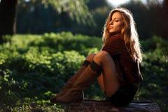 Giovane donna sexy che si siede sulla posa del libro macchina Fotografia Stock Libera da Diritti