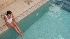 Giovane donna sexy in costume da bagno bianco che si siede dallo stagno con acqua blu archivi video