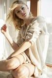 Giovane donna sexy esile in maglione marrone contro la finestra Fotografia Stock