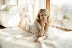 Giovane donna sexy esile in maglione marrone contro la finestra Fotografia Stock Libera da Diritti