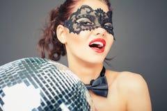 Giovane donna sexy nella maschera di carnevale che tiene la palla della discoteca Fotografia Stock