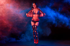 Giovane donna sexy nella striptease erotica di dancing di usura del feticcio in night-club Donna sexy nuda nel vestito di manifes Fotografia Stock