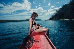 Giovane donna sexy sulla barca nei tropici Immagine Stock