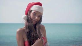 Giovane donna sexy vicino alla piscina in cappello di Santa che celebra nuovo anno ed il Natale video d archivio