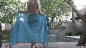 Giovane donna snella al bikini che va alla piscina su tropicale la località di soggiorno di Bali Indonesia video d archivio
