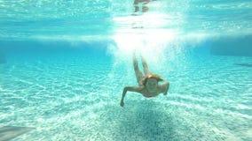 Giovane donna snella che salta nello stagno e che nuota sotto l'acqua video d archivio