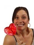 Giovane donna soddisfatta del lollipop a forma di del cuore Fotografia Stock