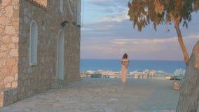Giovane donna sola che esamina il cielo di sera sopra il mare Vacanza al centro balneare stock footage