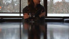 Giovane donna sola coperta in coperta che prova a scaldarsi con vetro del cognac stock footage