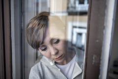 Giovane donna sola depressa infelice attraente che sembra preoccupata e triste attraverso la finestra a casa immagine stock