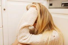 Giovane donna sola triste che si siede nella cucina Fotografie Stock